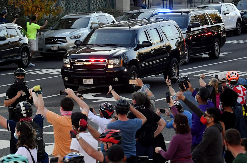 TOPSHOT - People react as the motorcade carrying US President Donald Trump returns to the White House on November 7, 2020 in Washington, DC., after Joe Biden was declared the winner of the 2020 presidential election. - Joyous celebrations erupted in Washington on Saturday after Joe Biden was declared winner of the US presidency, as several people poured into the streets of the US capital -- some of them chanting, cheering and singing in front of the White House. (Photo by Olivier DOULIERY / AFP) (Photo by OLIVIER DOULIERY/AFP via Getty Images)