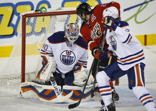 Edmonton Oilers goalie Devan Dubnyk, left, makes a save on a shot from Calgary Flames' Lee Stempniak, center, as Jeff Petry tries to pull him away during second period NHL hockey action in Calgary, Alberta. (AP Photo/The Canadian Press, Jeff McIntosh)