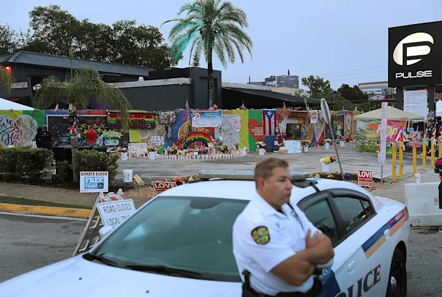 <p>A police car stands guard as people visit the memorial to the victims of the mass shooting setup around the Pulse gay nightclub one year after the shooting on June 12, 2017 in Orlando, Florida. (Joe Raedle/Getty Images) </p>