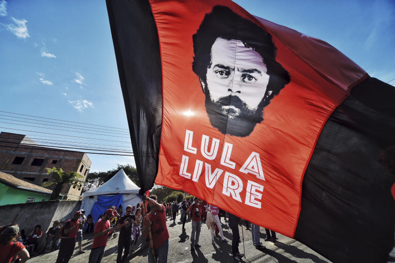 """A supporter of ex-President Luiz Inacio Lula da Silva holds a flag that reads in Portuguese: """"Free Lula,"""" in front of the Federal Police Department where Da Silvia is serving jail time in Curitiba, Brazil, Sunday, July 8, 2018. A Brazilian appeals court judge has ordered Da Silva released from jail on Sunday, July 8, 2018, but another judge has asked the police to hold off on the order. (AP Photo/Denis Ferreira Netto)"""