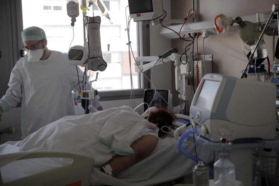 A nurse tends to a patient affected by the COVID-19 virus in the ICU unit at the Charles Nicolle public hospital, Thursday, April 15, 2021 in Rouen, France. A renewed crush of COVID-19 cases is again forcing intensive care units across France to grapple with the macabre mathematics of how to make space for thousands of critically ill patients (AP Photo/Christophe Ena)