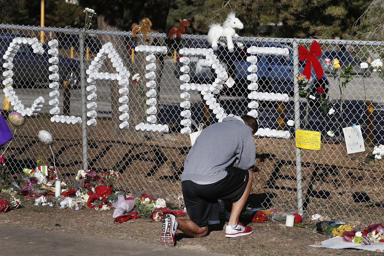 "Parker Semin, a 2011 Arapahoe High School graduate, prays at a makeshift memorial bearing the name of wounded student Claire Davis, who was shot by a classmate during school three days earlier in an attack, in front of Arapahoe High School in Centennial, Colo., Monday, Dec. 16, 2013. Semin said he came by to pray for the ""speedy recovery"" of Davis, age 17, who was shot in the head at close range with a shotgun, and remains in a coma. (AP Photo/Brennan Linsley)"