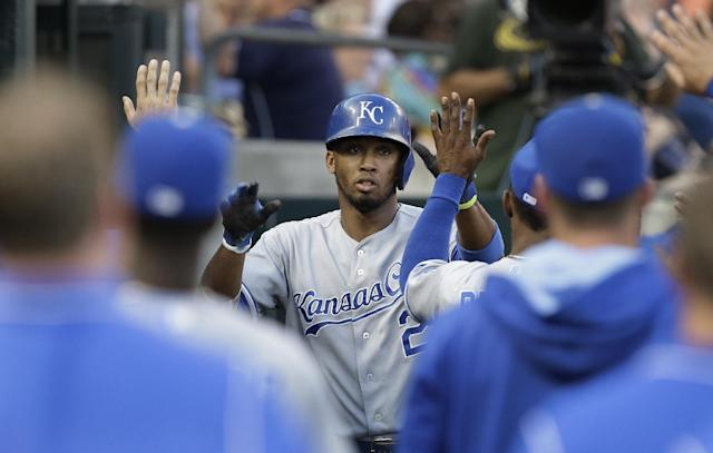 Kansas City Royals' Alcides Escobar (2) celebrates with teammates after scoring on a Omar Infante single against the Detroit Tigers in the fifth inning of a baseball game in Detroit, Monday, June 16, 2014. (AP Photo/Paul Sancya)
