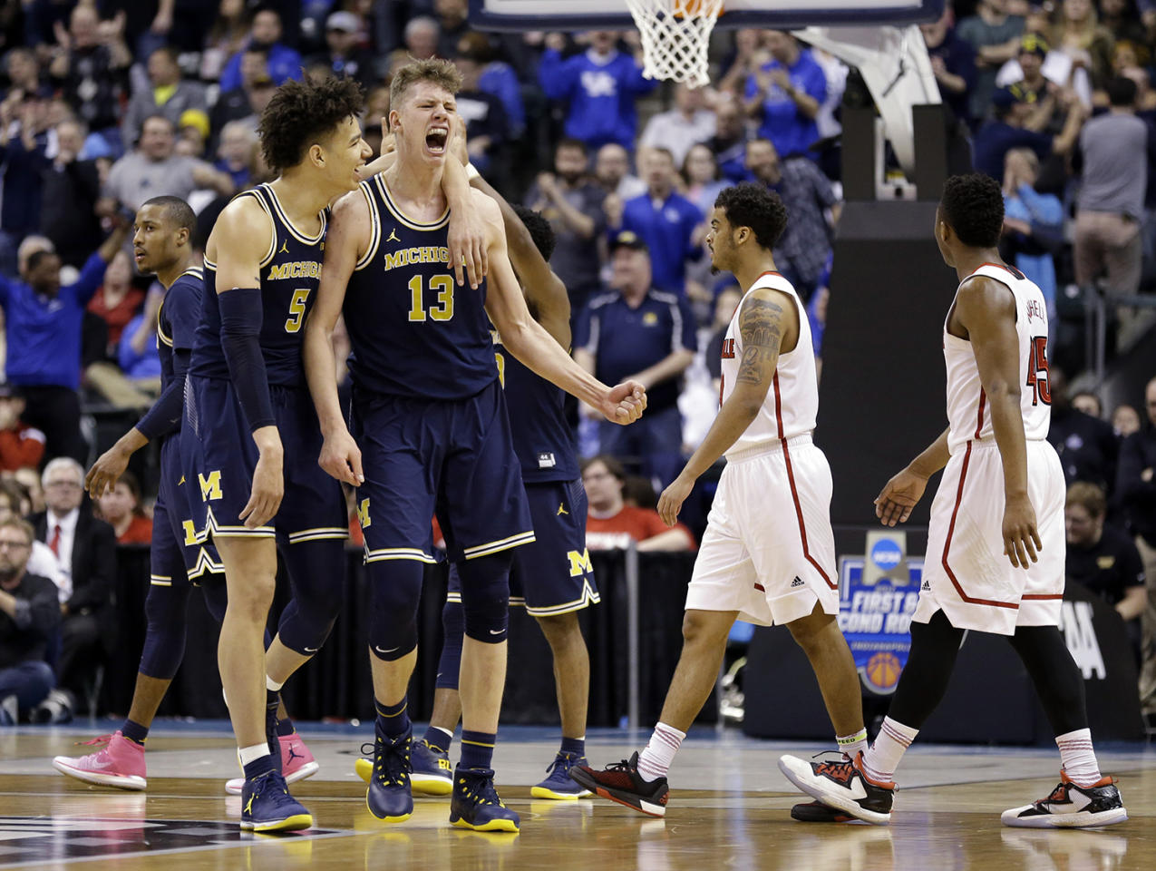 <p>Michigan forwards D.J. Wilson (5) and Moritz Wagner (13) celebrates during the second half of a second-round game against Louisville in the men's NCAA college basketball tournament in Indianapolis, March 19, 2017. Michigan defeated Louisville 73-69. (Photo: Michael Conroy/AP) </p>