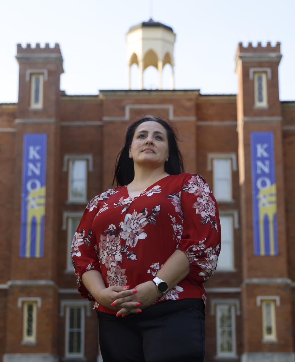 """Tianna Cervantez, Assistant Dean of Diversity and Inclusion at Knox College, stands for a portrait on the college campus, Thursday, June 17, 2021, in Galesburg, Ill. Cervantez, a member of the school board and legacy of the Mexican railroad camps, saw in people she and her family had known for generations, the angry opposition to a resolution acknowledging """"institutionalized racism"""" in policing, hiring, public health and other facets of community life. (AP Photo/Shafkat Anowar)"""