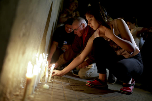 <p>Locals place candles outside the Polytechnic School during a vigil in Rosario, Argentina, Wednesday, Nov. 1, 2017. Five victims killed in the bike path attack near the World Trade Center in New York were part of a group of friends celebrating the 30th anniversary of their graduation from the Polytechnic School of Rosario, Argentina. (Photo: Natacha Pisarenko/AP) </p>