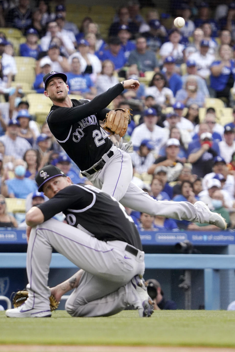 Colorado Rockies second baseman Ryan McMahon, top, attempts to throw out Los Angeles Dodgers' Chris Taylor at first as starting pitcher Kyle Freeland watches during the first inning of a baseball game Saturday, July 24, 2021, in Los Angeles. Taylor was safe at first on the play. (AP Photo/Mark J. Terrill)