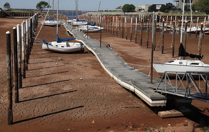 FILE - In this Sept. 30, 2011 file photo, Sailboats and a floating dock lie on the dry, cracked dirt in a harbor at Lake Hefner in Oklahoma City as drought continues to be a problem across the state. The relentless, weather-gone-crazy type of heat that has blistered the United States and other parts of the world in recent years is so rare and off-the-charts that it can't be anything but man-made global warming, a new statistical analysis from a top government scientist says.(AP Photo/Sue Ogrocki, File)