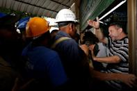 A bakery worker (R) tries to control the crowd as people queue to buy bread in Caracas July 21, 2016. REUTERS/Carlos Garcia Rawlins