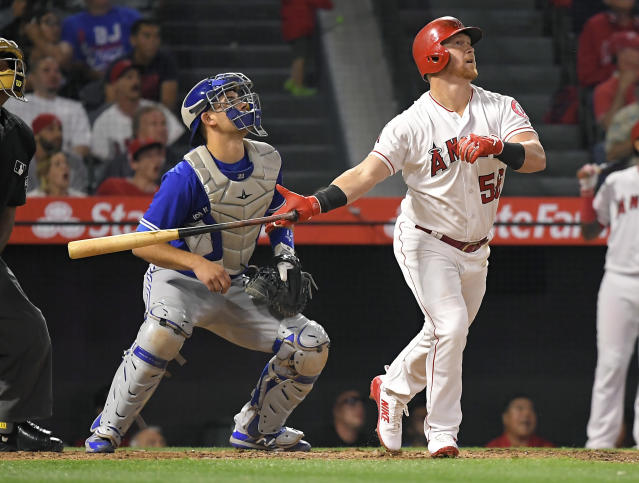 Los Angeles Angels' Kole Calhoun watches his two-run home run next to Toronto Blue Jays catcher Luke Maile during the fourth inning of a baseball game Thursday, June 21, 2018, in Anaheim, Calif. (AP Photo/Mark J. Terrill)