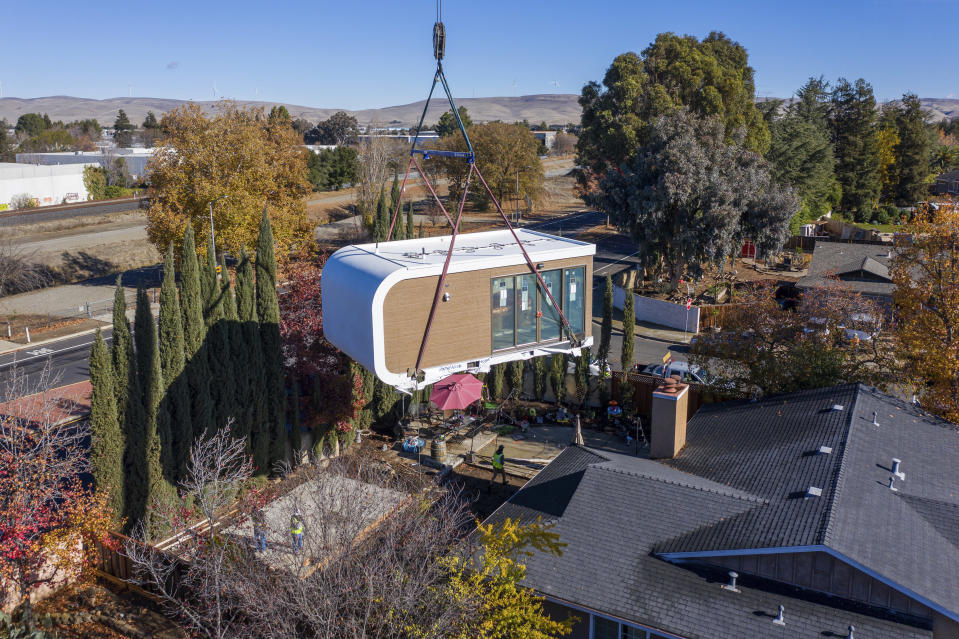 This photo provided by Mighty Buildings shows a 3D-printed housing module being delivered. Most of the modules built by Mighty Buildings are assembled in the factory, transported by truck to the owner's property, then put into place using a crane. (Courtesy of Mighty Buildings via AP)