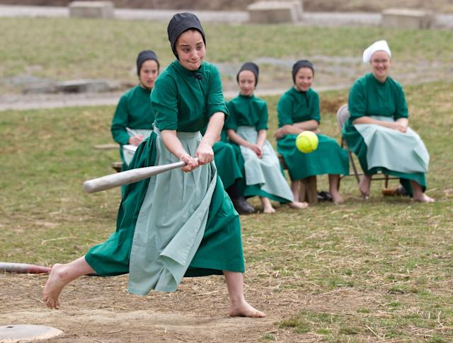 Amish girls play softball after class during an end of the school year celebration on Tuesday, April 9, 2013 in Bergholz, Ohio. The celebration was also part of a farewell picnic for four women and one man from this tight-knit group in rural eastern Ohio who will enter prison on Friday, April 12, joining nine already behind bars on hate crimes convictions for hair- and beard-cutting attacks against fellow Amish. (AP Photo/Scott R. Galvin)