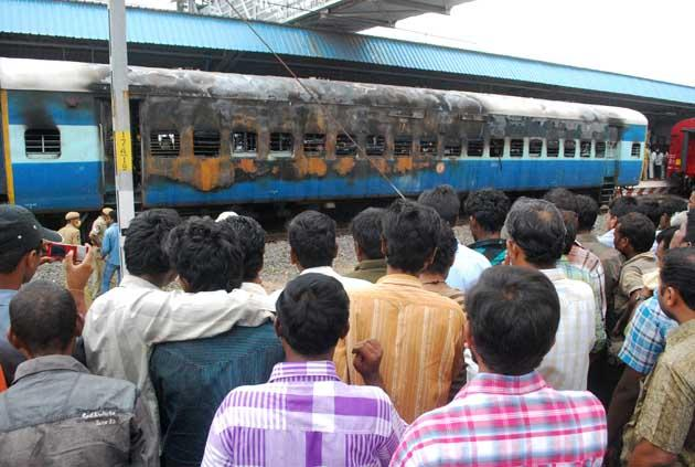 Bystanders gather to look at a gutted train carriage, which caught fire from an electrical short circuit killing at least 32, in Nellore on July 30, 2012. At least 32 people were killed July 30 when a fire ripped through a coach on an express train as it carried sleeping passengers to the southern Indian city of Chennai, officials said. AFP PHOTO/STR
