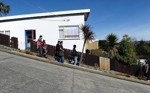 Tourists walk along one of the world's steepest street in Dunedin, New Zealand - Credit: AFP/Paul Ellis