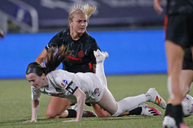 Portland Thorns midfielder Lindsey Horan, rear, reacts after taking down Washington Spirit midfielder Rose Lavelle during the second half of an NWSL Challenge Cup soccer match at Zions Bank Stadium on Sunday, July 5, 2020, in Herriman, Utah. (AP Photo/Rick Bowmer)