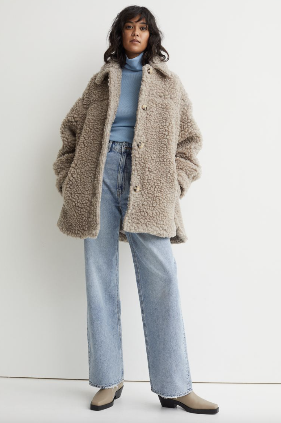 model with black hair posing in beige Faux Shearling Shirt Jacket and jeans