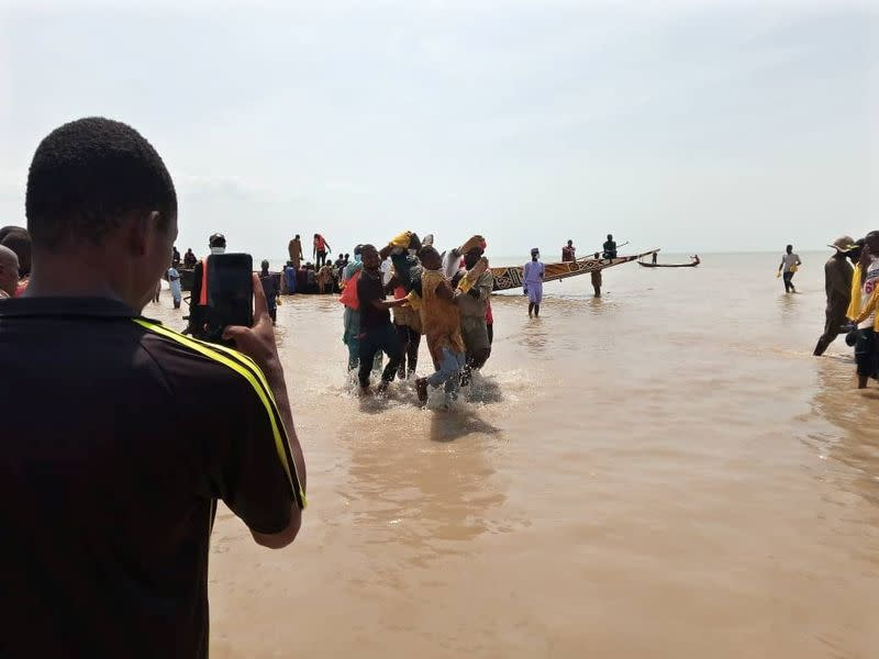 A man takes a picture as the body of one of the victims of a boat accident is being retrieved from the boat in Kebbi