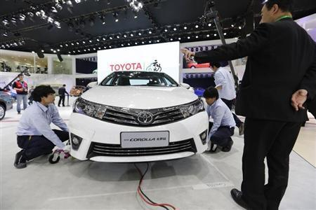 Staff members place a new Toyota COROLLA car for display at Auto China 2014 in Beijing