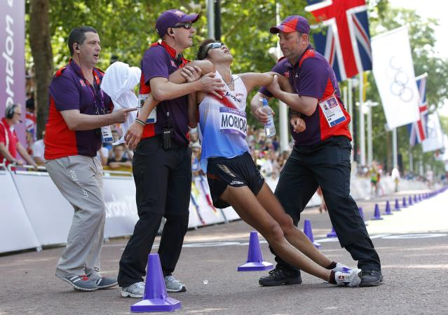 Japan's Koichiro Morioka is helped by officials after staggering across the finish line in the men's 50km race walk during the London 2012 Olympic Games at The Mall August 11, 2012. Russia's Sergey Kirdyapkin won the gold ahead of Australia's Jared Tallent who won silver and China's Si Tianfeng who took bronze. REUTERS/Laszlo Balogh (BRITAIN - Tags: SPORT ATHLETICS OLYMPICS TPX IMAGES OF THE DAY)