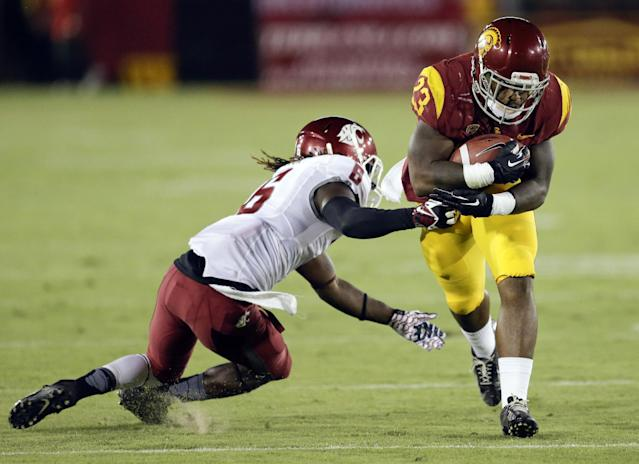 Southern California running back Tre Madden breaks away from Washington State cornerback Damante Horton during the first half of an NCAA college football game in Los Angeles, Saturday, Sept. 7, 2013. (AP Photo/Chris Carlson)