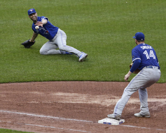 Toronto Blue Jays starting pitcher J.A. Happ, left, tosses the ball to first baseman Justin Smoak, right, to throw out New York Mets' Luis Guillorme during the fifth inning of a baseball game Wednesday, May 16, 2018, in New York. (AP Photo/Frank Franklin II)