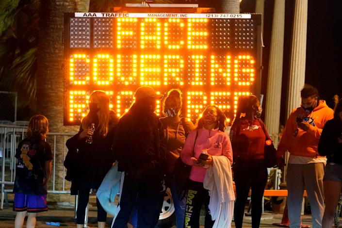 A sign encourages visitors to wear face masks amid the COVID-19 pandemic Friday, Feb. 19, 2021, in Santa Monica, Calif.