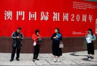 People stand in front of a poster celebrating the 20th anniversary of the former Portuguese colony's return to China in Macau