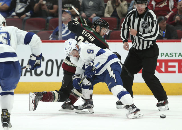 Tampa Bay Lightning's Tyler Johnson (9) and Arizona Coyotes' Derek Stepan battle for the puck during the second period of an NHL hockey game, Saturday, Oct. 27, 2018, in Glendale, Ariz. (AP Photo/Ralph Freso)