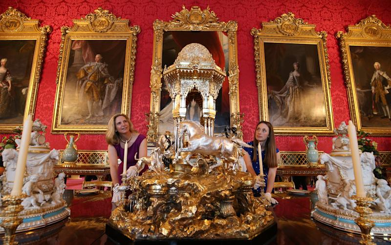 A pair of Royal Collection employees adjust placings at a recreation of a Victorian dinner in the State Dining Room featuring the Alhambra fountain (centre) at the exhibition to mark the 200th anniversary of the birth of Queen Victoria for the Summer Opening of Buckingham Palace, London. (Photo by Jonathan Brady/PA Images via Getty Images)