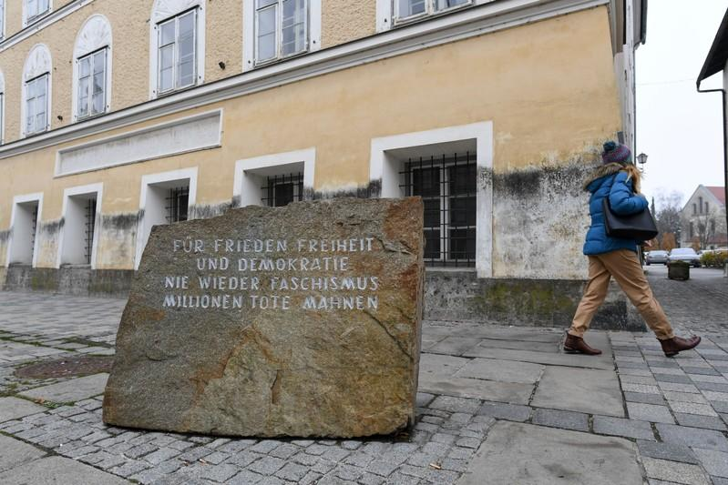 A woman walks past a memorial in front of Adolf Hitler's birth-house in Braunau