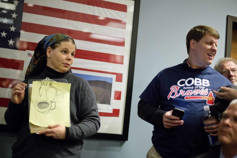 In this Nov. 26, 2013 photo, Amy Barnes, left, of Marietta, Ga., who is against the Atlanta Braves building a new baseball stadium in Cobb County, holds a drawing depicting taxes being flushed down the toilet as she waits in line next to Andrew Windham, right, of Acworth, Ga., a proponent of the new stadium, to sign up to speak during the Cobb County commission hearing on the subject, in Marietta, Ga. A deal for hundreds of millions of dollars in public money to draw the Atlanta Braves north of their downtown home is pitting conservative tea party activists against the elected and civic leaders in the staunch Republican county, with opponents saying the use of public money to help a private business is not what American capitalism should be about. (AP Photo/David Goldman)