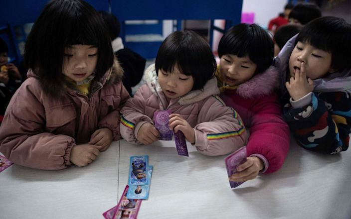 Children play cards in their dormitory - NICOLAS ASFOURI/AFP