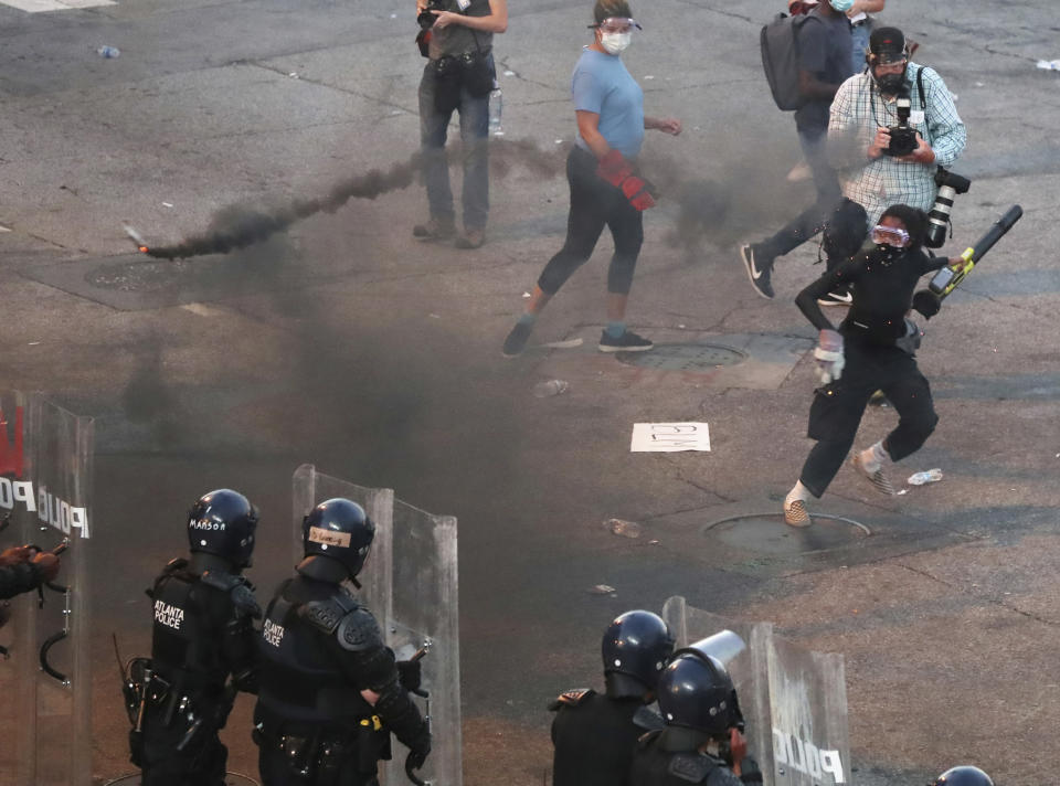 Protesters throw a burning object at advancing law enforcement officials on Centennial Olympic Park Drive at Olympic Park, Tuesday, June 2, 2020, in Atlanta, after curfew during a fifth day of protests over the death of George Floyd. (Curtis Compton/Atlanta Journal-Constitution via AP)