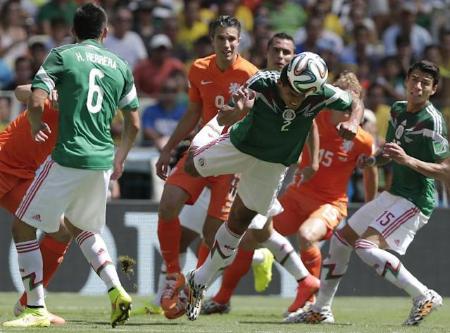 Mexico's Francisco Rodriguez heads the ball in defense between Netherlands' Robin van Persie, center, and Dirk Kuyt (15) during the World Cup round of 16 soccer match between the Netherlands and Mexico at the Arena Castelao in Fortaleza, Brazil, Sunday, June 29, 2014. A right is Mexico's Hector Moreno, at left, Mexico's Hector Herrera.(AP Photo/Marcio Jose Sanchez)
