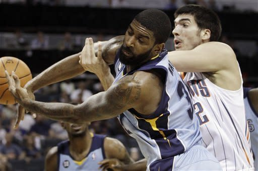 Memphis Grizzlies' O.J. Mayo, left, and Charlotte Bobcats' Byron Mullens, right, battle for a rebound during the first half of an NBA basketball game in Charlotte, N.C., Friday, April 20, 2012. (AP Photo/Chuck Burton)