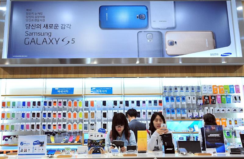 Visitors look at Samsung Electronics smartphones at a showroom in Seoul on April 29, 2014 (AFP Photo/Jung Yeon-Je)