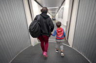 Celestina Ramirez, a migrant from Honduras, walks the jetway with her son, Yancarlos Amaya, 5, toward a plane in Houston that will take them to Baltimore at George Bush International Airport, Wednesday, March 24, 2021. A few days ago, Yancarlos was walking along a muddy river bank after crossing the Rio Grande and landing on the U.S. side of the border with Mexico. Ramirez said they turned themselves in to U.S. Border Patrol officers and later spent hours in custody, a night under a bridge and three more days in a detention facility. (AP Photo/Julio Cortez)