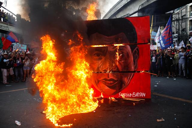A cubic effigy painted with the face of President Rodrigo Duterte is set on fire by activists during a rally.