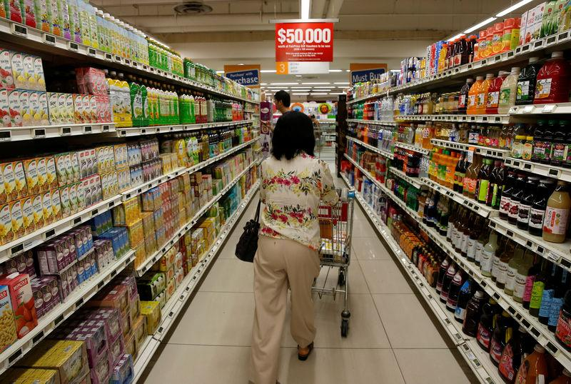 A woman pushes a shopping cart at a supermarket in Singapore