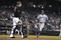 Los Angeles Dodgers' Chris Taylor (3) steals home plate on a double steal in front of Arizona Diamondbacks catcher Carson Kelly during the second inning of a baseball game Saturday, July 31, 2021, in Phoenix. (AP Photo/Rick Scuteri)