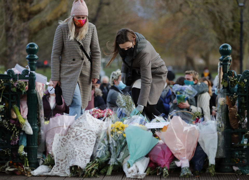 People leave floral tributes, at the band stand in Clapham Common, after a vigil for Sarah Everard was officially cancelled, in London, Saturday, March 13, 2021. A serving British police officer accused of the kidnap and murder of a woman in London has appeared in court for the first time. Wayne Couzens, 48, is charged with kidnapping and killing 33-year-old Sarah Everard, who went missing while walking home from a friend's apartment in south London on March 3. (AP Photo/Frank Augstein)