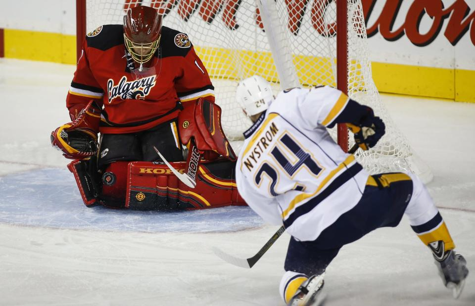 Nashville Predators' Eric Nystrom, right, takes shot on Calgary Flames goalie Jonas Hiller, from Switzerland, during the first period of an NHL hockey game Friday, Oct. 31, 2014, in Calgary, Alberta. (AP Photo/The Canadian Press, Jeff McIntosh)