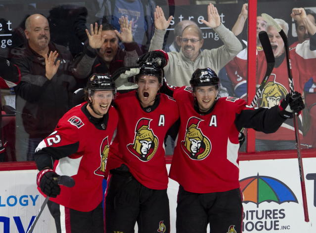 Ottawa Senators right wing Mark Stone celebrates his game-winning goal with teammates Thomas Chabot (72) and center Matt Duchene (95) during overtime of an NHL game in Ottawa, Ontario, Saturday, Oct. 20, 2018. The Senators won, 4-3, in overtime. (Adrian Wyld/The Canadian Press via AP)