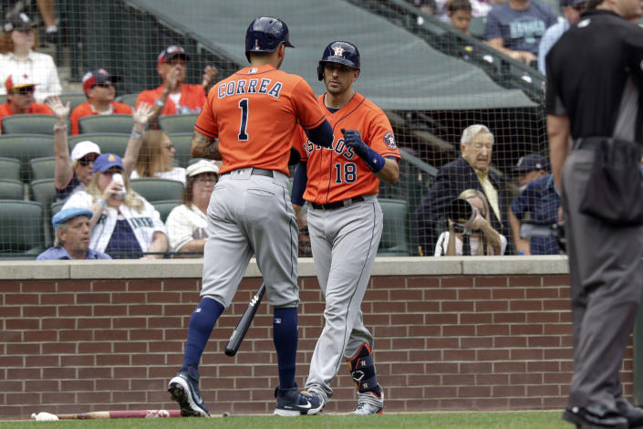 Houston Astros' Carlos Correa celebrates with teammate Jason Castro after scoring a run during the second inning of a baseball game against the Seattle Mariners, Wednesday, July 28, 2021, in Seattle. (AP Photo/Jason Redmond)