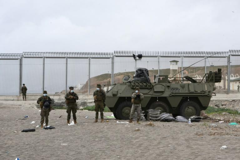 Spanish soldiers stand guard at the border fence between Morocco and Spain