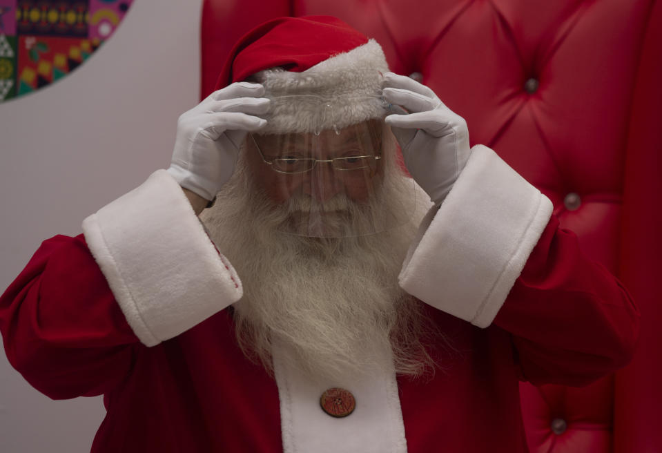 Santa adjusts his face shield, worn to protect against COVID-19, where he is to be photographed with children at a shopping mall in Johannesburg, South Africa, Tuesday, Dec. 22, 2020. Coronavirus restrictions allow for Children to meet with Santa, but they have to respect social distancing and sit separately. (AP Photo/Denis Farrell)