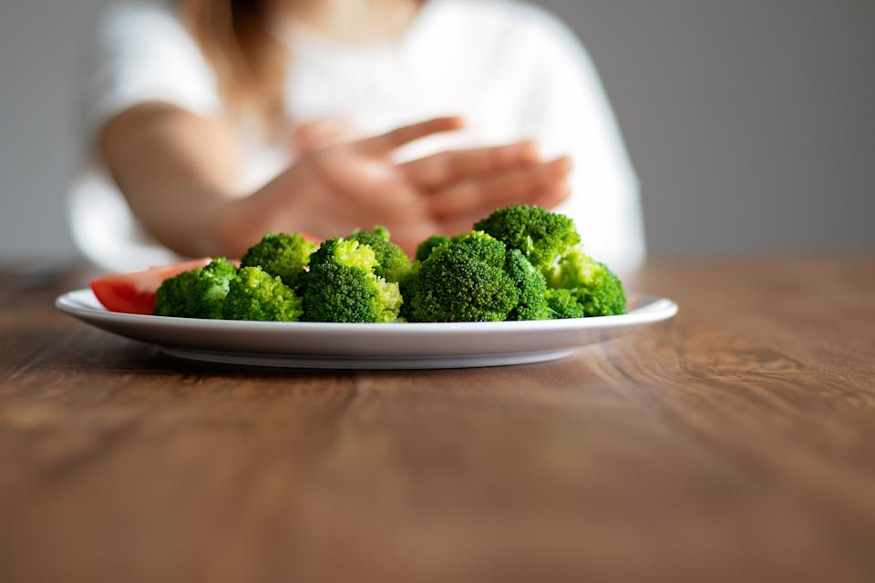 No vegan diet concept. Teen girl pushing away plate with broccoli and other vegetables refusing to eat. Food waste. Copy space. Selective focus on food.