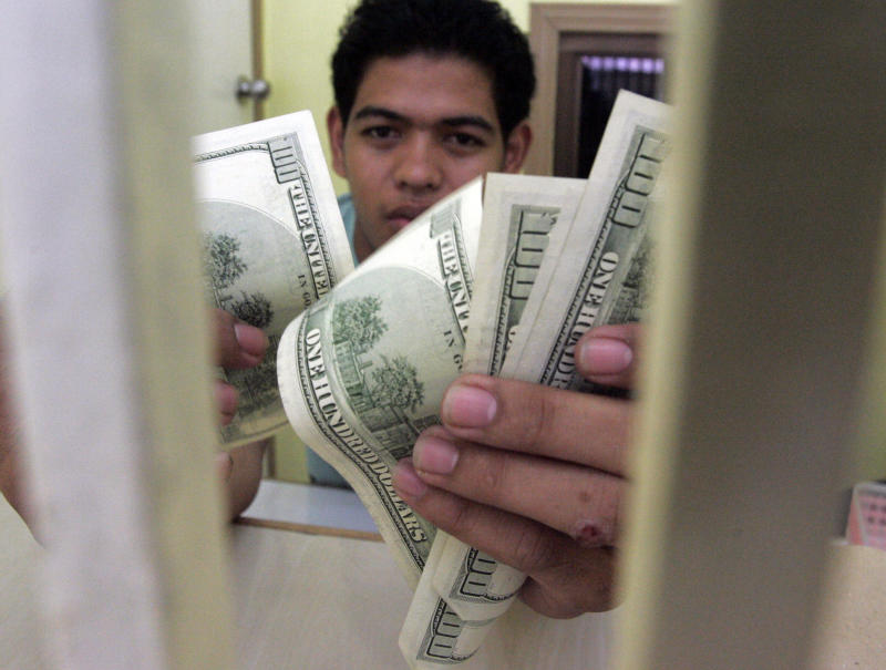 A man counts U.S. dollar bills inside a security steel bars in a money exchange shop Tuesday, Aug. 9, 2011 in Manila, Philippines. The peso gain a little amid the global market meltdown.  (AP Photo/Pat Roque)
