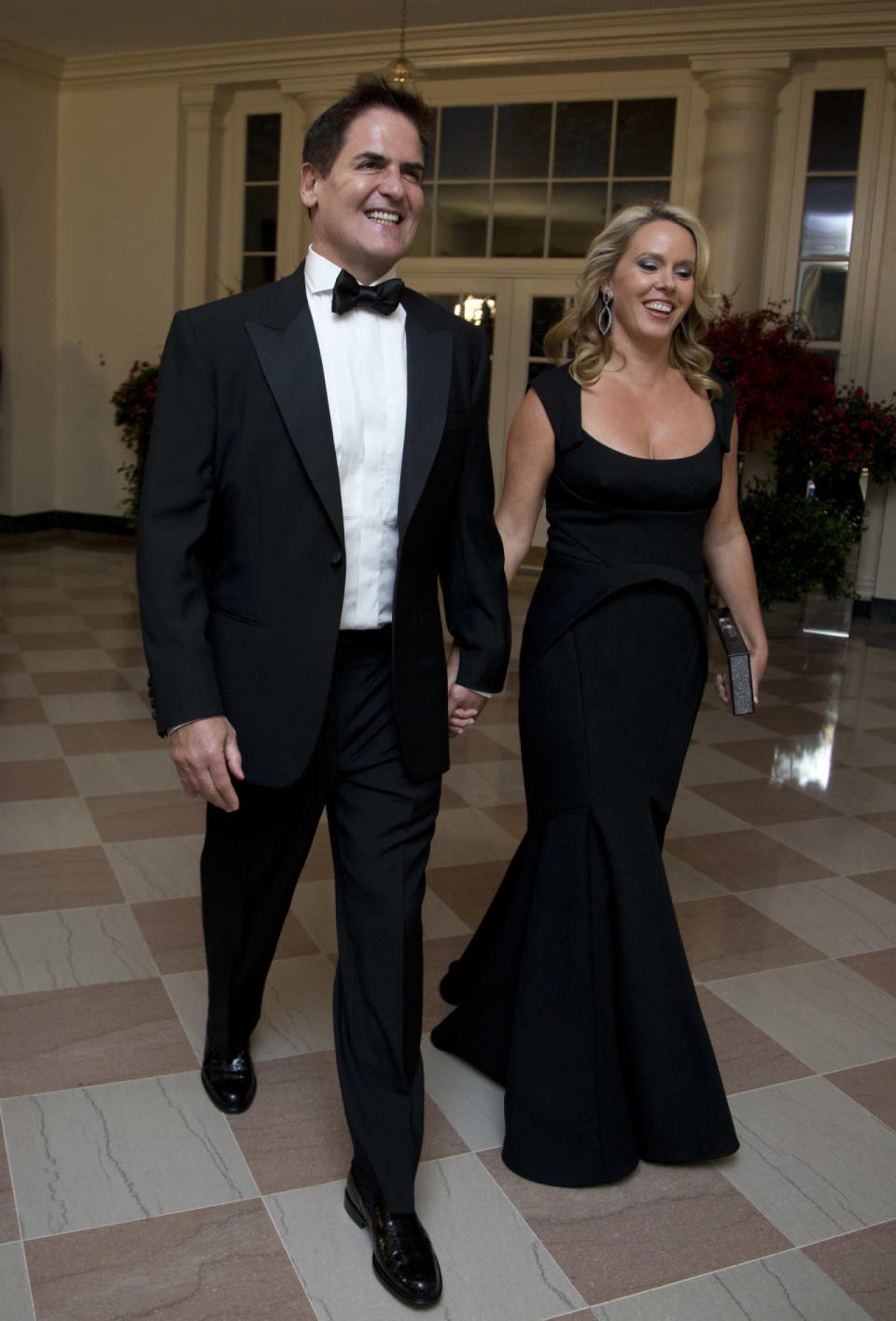 NBA's Dallas Maverick owner Mark Cuban and his wife Tiffany Cuban at the State Dinner in honor of Chinese President Xi Jinping, in the East Room of the White House in Washington, DC. Mark Cuban's wife Tiffany wore a similar silhouette to Michelle Obama's Vera Wang dress with a trumpet bottom on the skirt of her gown.