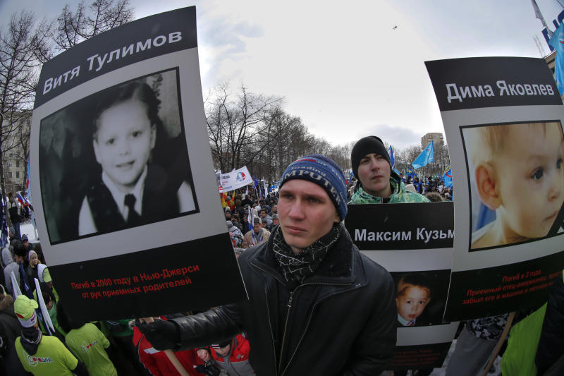 "Demonstrators hold portraits of adopted Russian children who died in U.S., during a massive rally in Moscow, Saturday, March 2, 2013. Russia voiced strong skepticism Saturday about the U.S. autopsy on Max Shatto, a 3-year-old adopted Russian boy in Texas and demanded further investigation as thousands rallied in Moscow to support the Kremlin ban on U.S. adoptions of Russian children. The poster at left reads: ""Vitya Tulimov died in 2000 in New Jersey at the hands of adoptive parents."" A poster at right reads ""Dima Yakovlev."" (AP Photo/Alexander Zemlianichenko)"